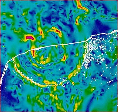 Карта гравитационной аномалии в районе кратера Чикшулуб. Красным и желтым обозначены зоны высокой гравитации, зеленым и синим низкой. Белая линия это берег полуострова Юкатан. Белые точки карстовые воронки. (по compulenta.ru)